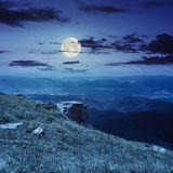 Boulders on the endge of mountain at night. View on high mountains from hillside covered with grass with few stones on the edge at night in full moon light Royalty Free Stock Photos