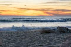 Boulders on Faro beach at sunset in Algarve, Portugal as waves break. With vivid orange yellow sky stock photos