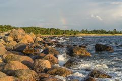 Boulders, forest, shore, evening light, sunset, clouds, blue sky and rainbow on the Baltic Sea Royalty Free Stock Photography