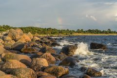 Boulders, forest, shore, evening light, sunset, clouds, blue sky and rainbow on the Baltic Sea Royalty Free Stock Photo