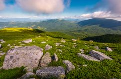 Boulders on grassy hill in summer. Lovely nature scenery under the cloudy sky in Carpathian mountains, Ukraine Stock Image