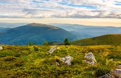 Boulders on grassy hill in summer. Lovely nature scenery under the cloudy sky in Carpathian mountains, Ukraine Royalty Free Stock Photo