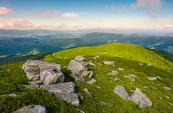 Boulders on a grassy slopes of Runa mountain. Lovely mountainous landscape on a cloudy summer day Stock Photos