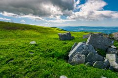 Boulders on a grassy slopes of Runa mountain. Lovely mountainous landscape on a cloudy summer day royalty free stock photos