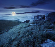 Boulders on hillside in high mountains at night. Huge boulders on the top edge of hillside with grass and dandelions in high mountains at night in full moon Stock Image