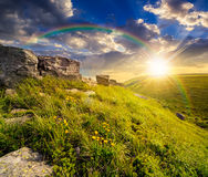 Boulders on hillside in high mountains at sunset. Huge boulders on the top edge of hillside with grass and dandelions in high mountains under the rainbow in Stock Image