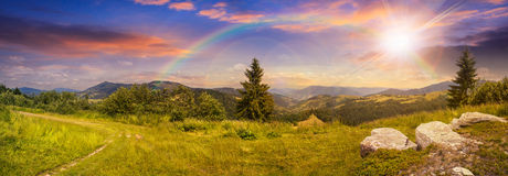 Boulders on hillside meadow in mountain at sunset with rainbow. Pnoramic collage  landscape. boulders on the meadow with path on the hillside and two pine trees Royalty Free Stock Photo