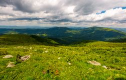 Boulders on the hillside in high mountains. Boulders on the hillside. mountain summer landscape. meadow with huge stones among the grass on top of the hill Stock Photography