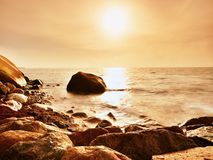 Boulders at island shore stick up from smooth sea. Stony coast defies to waves Royalty Free Stock Photo