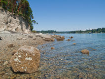 Boulders, pebbles and barnacles cover the shore Royalty Free Stock Photo