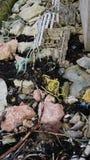 Seashore trash piled on riprap stock images