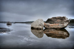 Boulders reflecting on water. Large boulders reflecting on lake in countryside Stock Photography