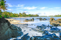 Boulders rest in a crystal clear lagoon on the tropical island of Rarotonga, Cook Islands. Boulders rest on the beach and in the waters of  crystal clear Muri Royalty Free Stock Image