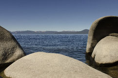 Boulders and Rocks Along a Lake Shoreline of Lake Tahoe. A view through the rocks and boulders of a high alpine lake in the mountains on a clear sunny day Royalty Free Stock Images