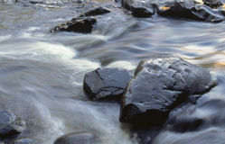 Boulders in a Rushing Stream. Water runs swiftly through the Dells of the Eau Claire River Stock Photos
