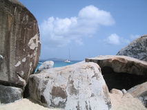 Boulders and Sailboat. A sailboat on Devil's Bay peeking over gigantic granite boulders at The Baths at Virgin Gorda, British Virgin Islands. If you can, please Royalty Free Stock Photography