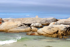 Boulders in the Sea. White boulders and small calm waves on a beach in Cape Town stock images