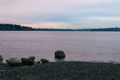 Boulders on the shore. Of a lake in a pink sunrise Royalty Free Stock Photos