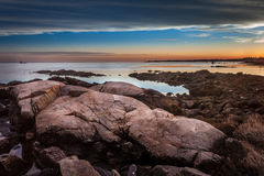Boulders On The Shore At Sunset With Lighthouse In The Distance Stock Photos