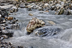 Boulders in a small mountain stream surrounded by flowing water long time exposure Royalty Free Stock Image