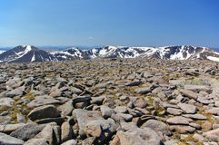 Boulders on the summit of Ben Macdui with snow-covered ridge in the background. Boulders and rocks on the summit of Ben Macdui with snow-covered mountain ridge Royalty Free Stock Photography