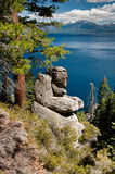 Boulders and trees next to Lake Tahoe with mountains Royalty Free Stock Images