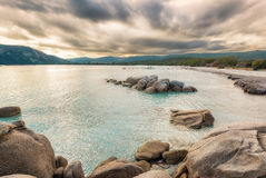 Boulders in a turquoise sea at Santa Giulia beach in Corsica Stock Photos