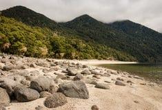 Boulders on white sand beach at lake Manapouri Stock Photos