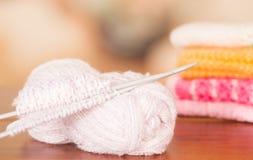 Boule blanche de fil de plan rapproché sur le bureau de table avec des aiguilles de tricotage en métal se trouvant à travers Images stock