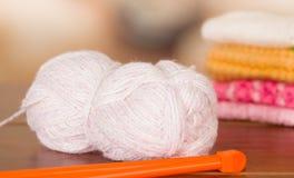Boule blanche de fil de plan rapproché sur le bureau de table avec les aiguilles de tricotage en bois se trouvant à côté de lui Image libre de droits