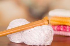 Boule blanche de fil de plan rapproché sur le bureau de table avec les aiguilles de tricotage en bois se trouvant à travers Photo stock