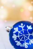 Boule bleue de Noël avec le fond d'or de neige d'ornement blanc de flocon avec les lumières colorées de fusée de confettis, l'esp Photos stock