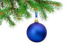 Boule bleue de Noël accrochant sur une branche d'arbre de sapin d'isolement Image stock