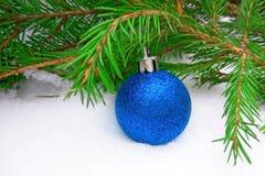Boule bleue de nouvelle année avec l'arbre de sapin vert sur le fond neigeux photo libre de droits