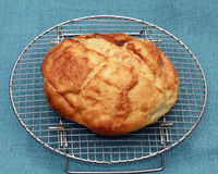Boule Bread Loaf on Cooling Rack with blue burlap. A boule bread loaf cools on a wire cooling rack against a blue burlap background Stock Photo