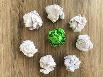 Boule chiffonnée de Livre vert parmi les boules blanches photos stock