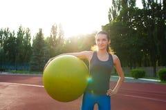 Boule convenable de participation sportive étonnante de jeune femme au stade au su Photos stock