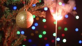 Boule décorée d'arbre de Noël avec un cierge magique brûlant à l'arrière-plan brouillé fabuleux clips vidéos
