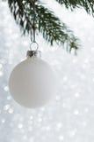 Boule décorative blanche sur l'arbre de Noël sur le fond de bokeh de scintillement Carte de Joyeux Noël Photos stock