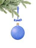 Boule décorative de Noël bleu de scintillement sur le ruban sur l'arbre vert i Image stock
