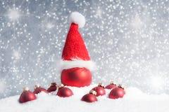 Boule d'arbre de Noël avec le chapeau de Santa dans la neige Photographie stock
