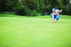 Boule d'inscription de joueur de golf sur le putting green Photo stock