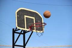 Boule de basket-ball dans le panier Images stock