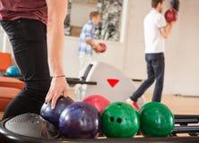 Boule de bowling de cueillette d'homme avec des amis dedans Photographie stock