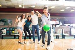Boule de bowling de lancement de garçon tandis qu'amis encourageant dans le club Image stock