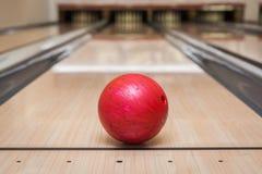 Boule de bowling rouge sur la voie au centre de bowling Images libres de droits