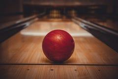 Boule de bowling rouge sur la voie au centre de bowling Image stock