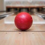 Boule de bowling rouge sur la voie au centre de bowling Photo libre de droits