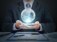 Boule de cristal de prise de main d'homme d'affaires avec la nuit de ville à l'intérieur images stock