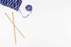 Boule de fil et du tricotage avec les aiguilles de tricotage en bois sur le fond blanc Image stock